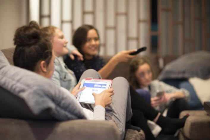 A family relaxes in their living room by watching TV and using social media.
