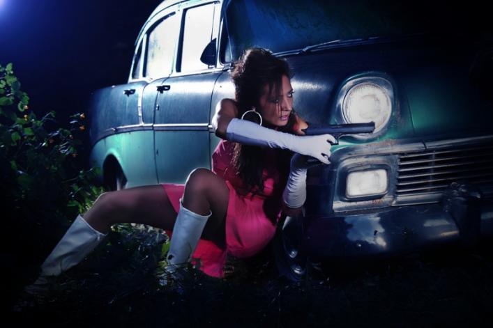 A movie action hero aims her gun at an enemy as she takes cover behind a car.