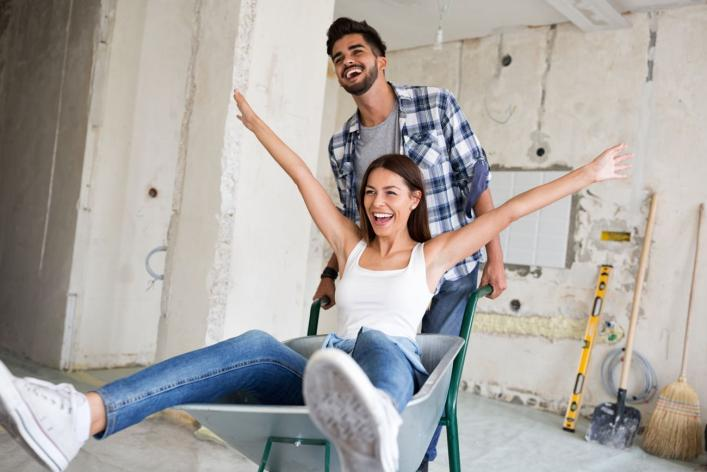 A man pushes a woman a wheelbarrow as this both celebrate their new renovation project.